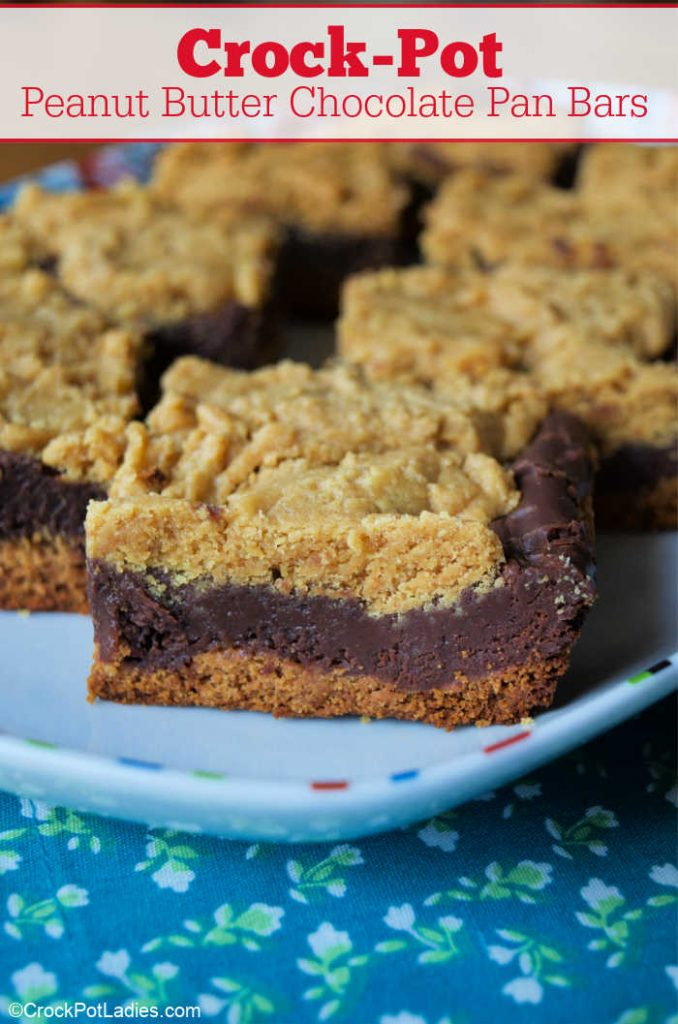 """A white platter with peanut butter and chocolate layered baked snack bars resting on a blue calico floral fabric with test overlay reading """"Crock-Pot Peanut Butter Chocolate Pan Bars""""."""