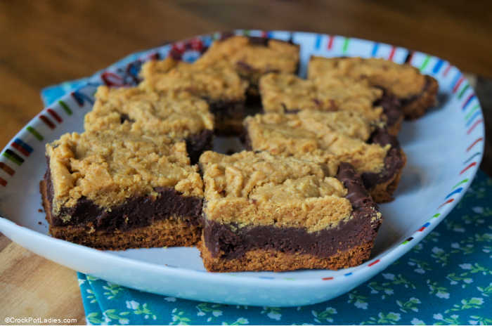 A white platter presenting peanut butter and chocolate layers baked snack bars resting on a blue floral fabric.
