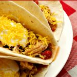 Crock-Pot Chicken Fajitas in flour tortillas topped with sour cream and shredded cheddar cheese